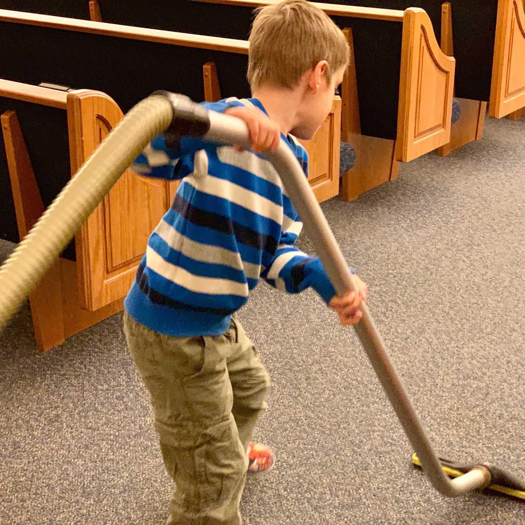Six-year-old vacuuming the church